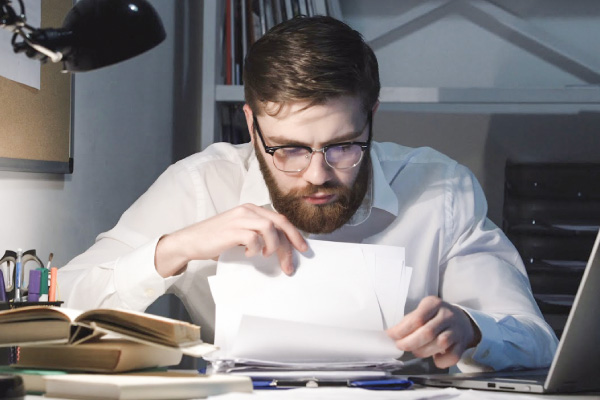 Ensimetri tarjoaa maksutonta neuvontaa aloittaville yrityksille. Kuvassa mies selaa papereita työpöydän ääressä.