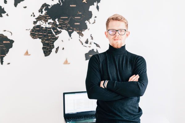 Palvelut toimiville yrittäjille. Kuvassa mies seisomassa taustallaan maailman kartta.