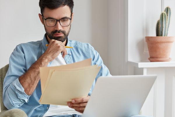 Palvelut rahoitukseen ja yritystukiin. Mies tutkimassa papereita, etualalla läppäri.